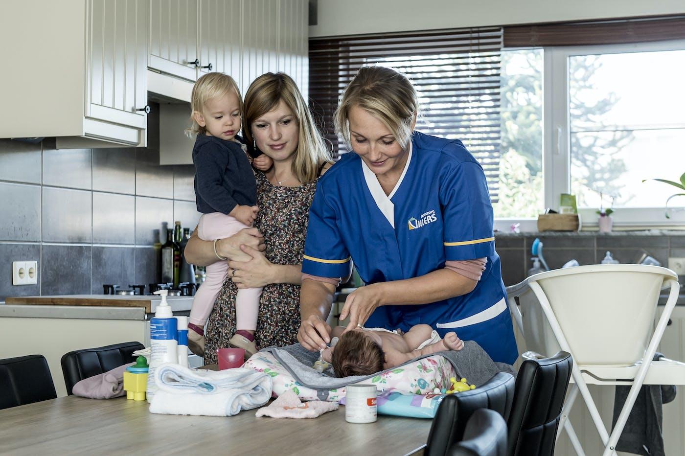 Verzorger en baby in keuken