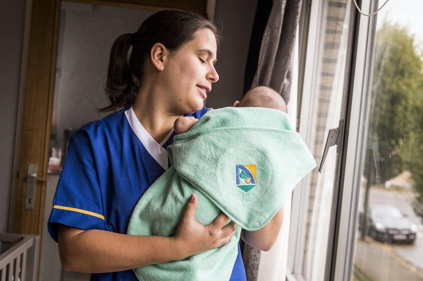 Verzorgster staat met baby aan raam