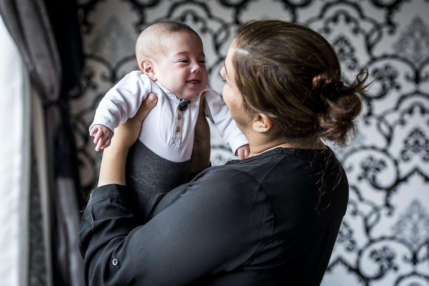 Verzorgster tilt baby op