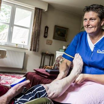 Verzorgster met been op schoot